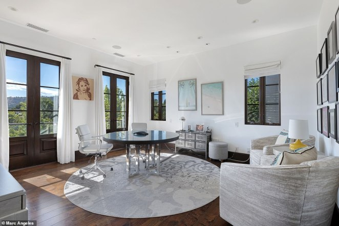Griffin's office offers natural light and light colored furniture for an airy feel. On the wall is a portrait of fellow comedian, the late, great Joan Rivers