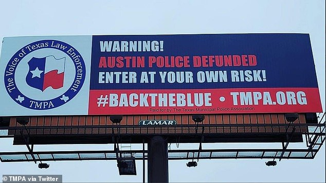Two billboards have appeared at the entrance to Austin, warning of police defunding
