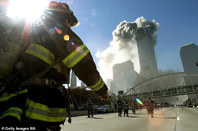 Firefighters walk towards one of the towers at the World Trade Center before it collapsed after a plane hit the building September 11, 2001