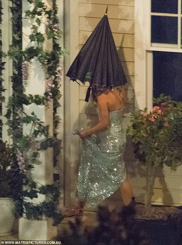 Careful: The beauty picked up her dress with one hand, as she made her way across the mansion's grounds