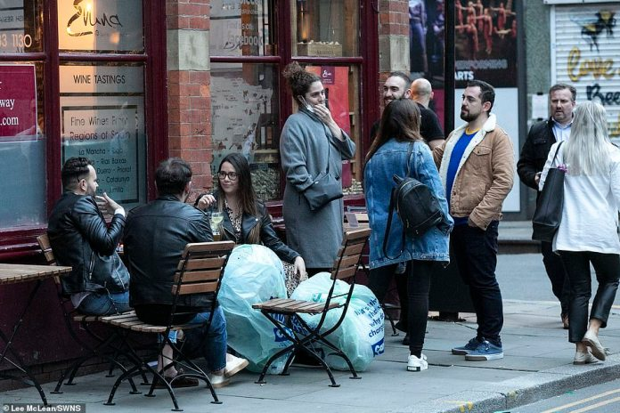 Others in the city gathered near to a wine bar as they enjoyed a night out with their friends