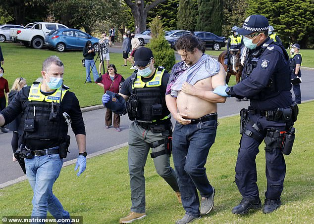 A man with his shirt ripped is taken away by police in Melbourne last week