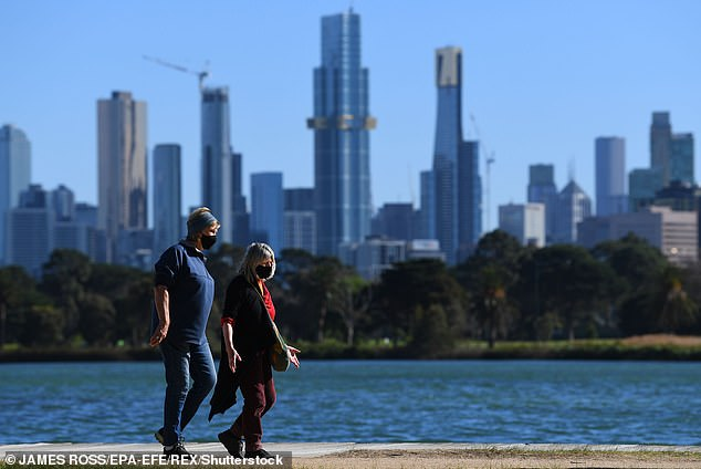 A man and a woman go for a walk during lockdownin Williamstown in Melbourne on Friday