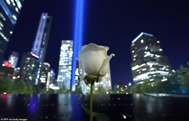A white rose appears on the 9/11 Memorial as the Tribute in Light Art installation shines in the night sky