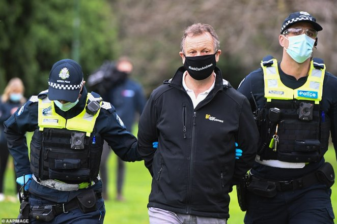 Two Victorian police officers lead another demonstrator away from the protest on Saturday