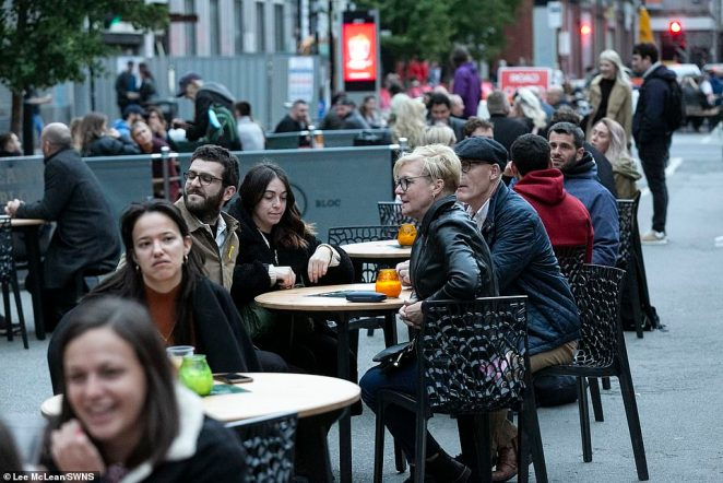 People in Manchester sit outside ahead of the introduction of new coronavirus rules on Monday