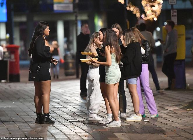 A group of girls gather in the street in Portsmouth to enjoy a late-night takeaway ahead of the 'rule of six' coming into force