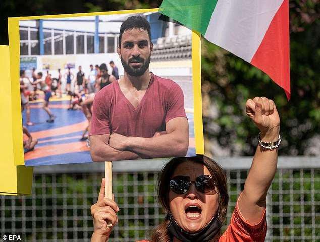 BERLIN:A supporter of the National Council of Resistance Iran (NWRI) and the Iranian Exile Society in Berlin holds a placard with the picture of Iranian wrestler Navid Afkari outside the Iranian embassy in Berlin, while protesting against his execution