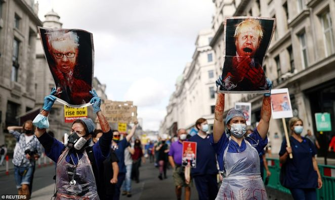 Frontline NHS workers, many of whom have been helping to fight the coronavirus pandemic, protest in London today demanding better wages. Protesters hold pictures of Prime Minister Boris Johnson and the Chancellor of the Duchy of Lancaster Michael Gove during the demonstration