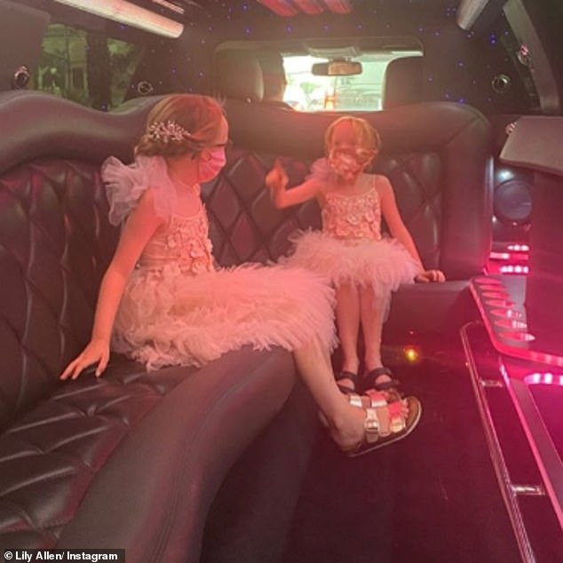 Adorable: Lily's daughters looked adorable in their matching pink floral dresses which featured a tulle skirt and complemented their masks perfectly