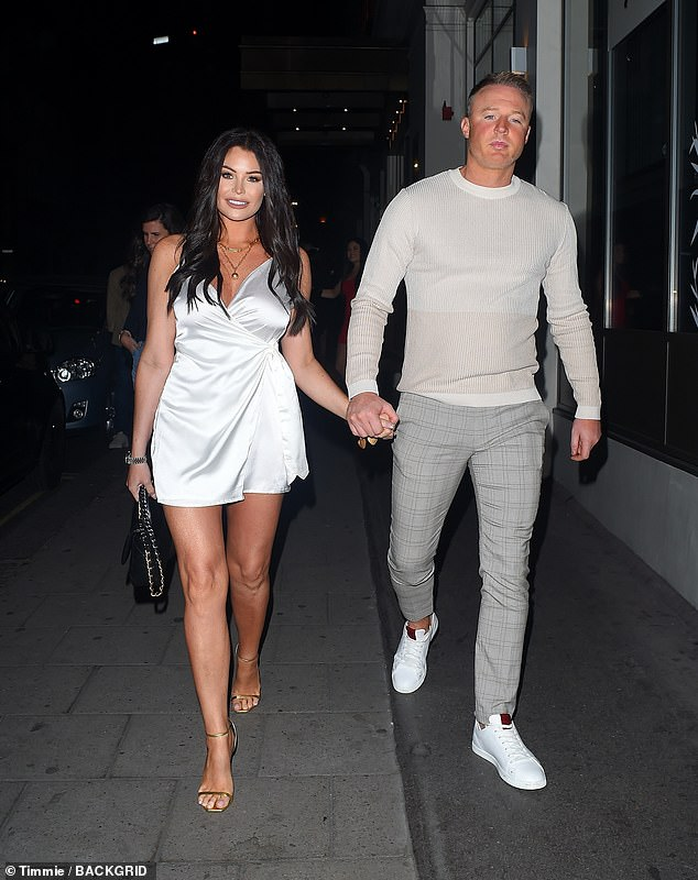 Stunning: Jess Wright looked effortlessly chic in a sleek white dress as she held hands with fiance William Lee-Kemp as they enjoyed a night out in London on Saturday