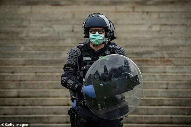 A police officer with riot gear stands outside the Shrine of Remembrance on Saturday. Authorities had hoped the poor weather would keep protesters inside