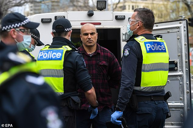 One protester was taken into the back of a police paddy wagon after he was arrested during the Freedom Walk rally in Melbourne