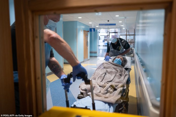 Members of the South Central Ambulance Services move an elderly patient from hospital to a care home near Portsmouth, south England on May 5, 2020