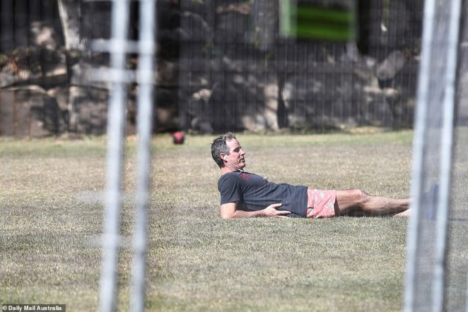 Pictured: A man inside the AFL hub laying on a patch of grass with a football in the background
