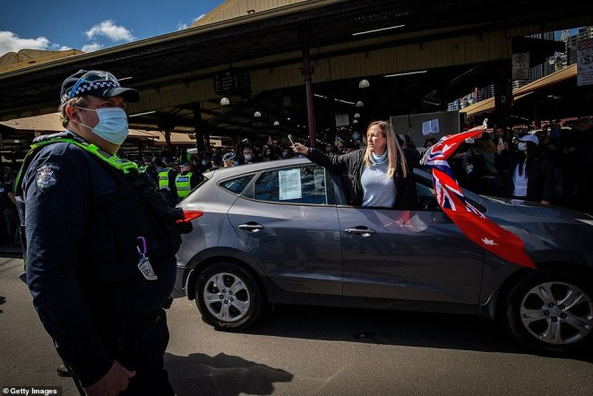 A woman hangs out of a car window near police wearing masks during the anti-lockdown protest