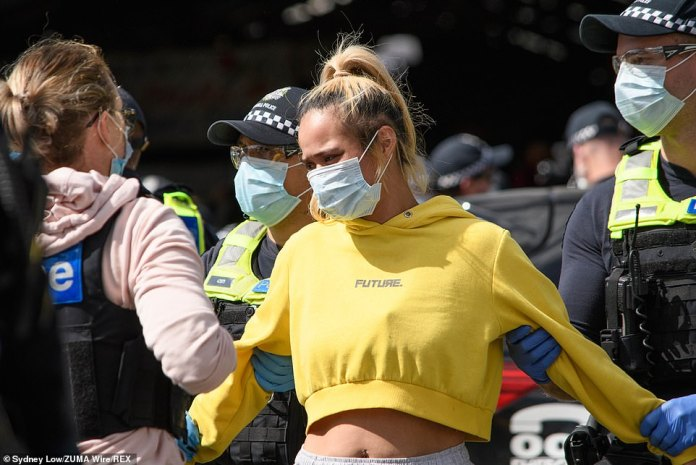 Victoria Police arrested 74 people and issued at least 176 infringement notices for breaching the Chief Health Officer directions at a protest in Melbourne' CBD on Sunday. A woman is pictured being detained by police