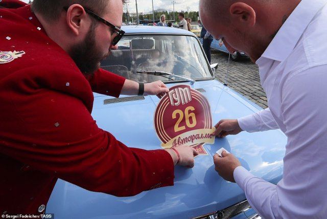 Two men place a GUM Motor Rally sticker on a blue Lada. The Lada was born out of a cooperation agreement between Russia and car manufacturer Fiat