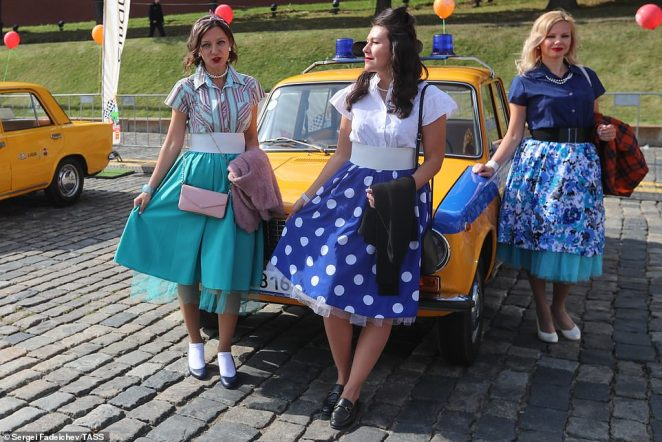 Many visitors to the show donned vintage outfits, with women opting for playful costumes as they posed next to a yellow and blue Lada