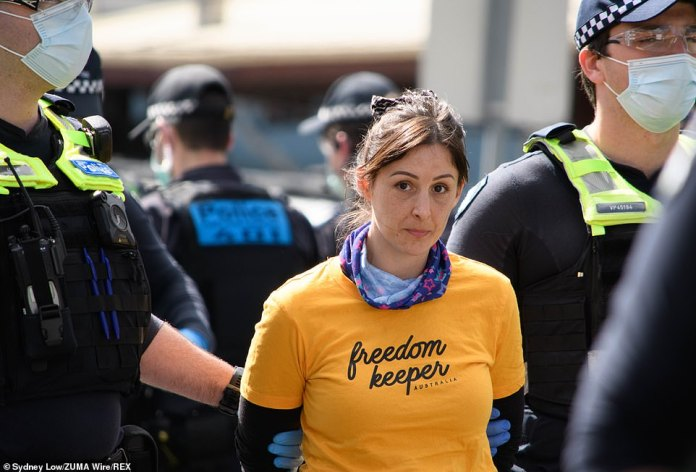 A woman wearing a 'freedom keeper' shirt was handcuffed and escorted away by officers as tensions spill over the Victorian Premier's coronavirus restrictions