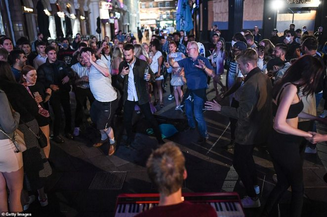LONDON: People are seen dancing to a keyboard player's music in Leicester Square on Saturday night ahead of Monday's rule changes