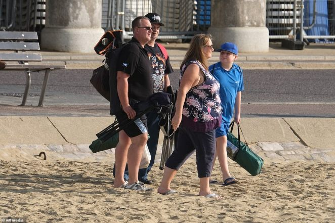 A group of people make their way onto the beach on the south coast as mercury levels push to 77F today across most parts of England