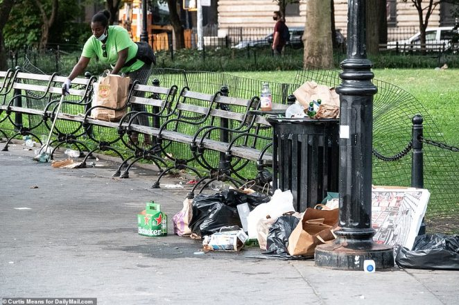 A park worker uses gloves and a trash picker to corral tons of waste leftover from the revelry on Saturday night