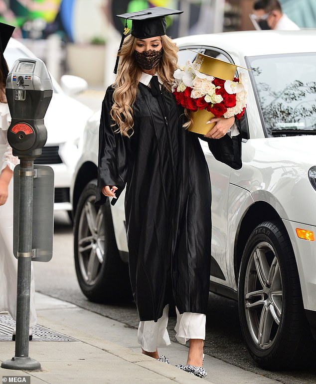 Celebration:Showing off her accomplishment, Farrah carried a gold box fashioned in the shape of a cap that held a sea of red and white roses accented with white orchids
