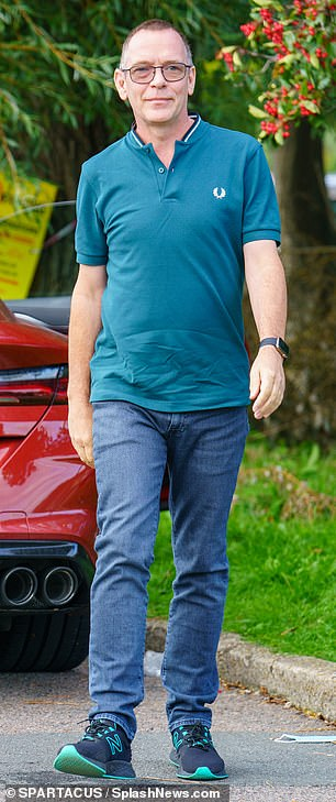 Laid back: The TV star cut a casual figure for the outing, sporting a teal polo shirt along with a pair of blue jeans as he went for a stroll in Hertfordshire