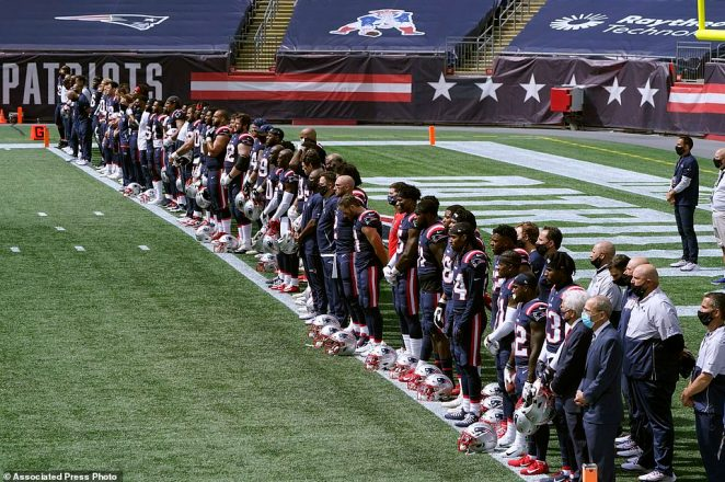 New England Patriots stand on the touchline before the start of their game on Sunday