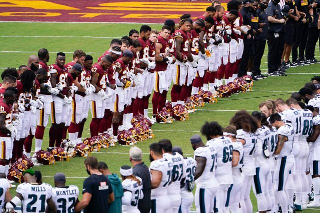 Members of the Washington Football Team and Philadelphia Eagles lock arms and form an oval on the field before the start their game