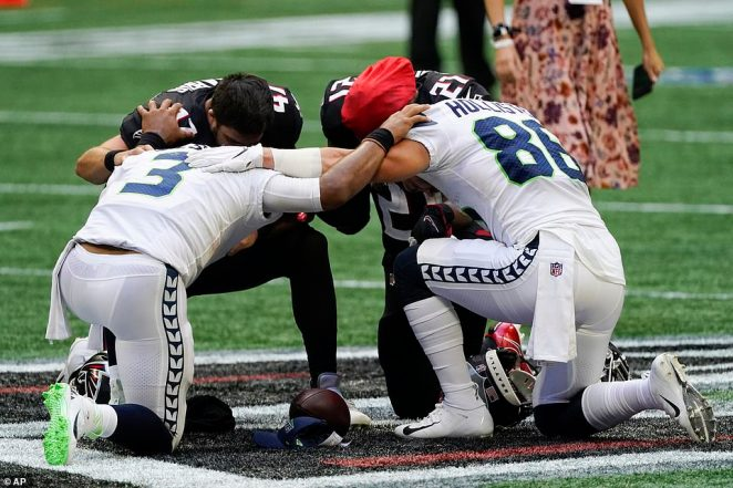 Seattle Seahawks quarterback Russell Wilson (3) and Seattle Seahawks tight end Greg Olsen (88) pray with Atlanta Falcons long snapper Josh Harris (47) and Atlanta Falcons running back Todd Gurley (21) in Atlanta
