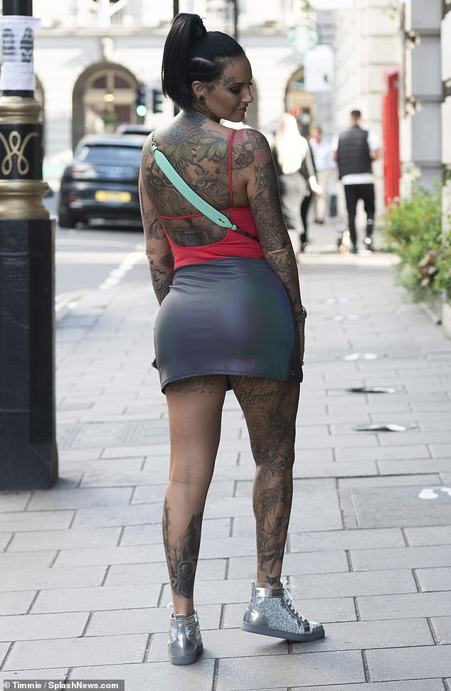 Incredible figure: In a bold move she decided to go braless and contained her ample assets in the strappy backless vest