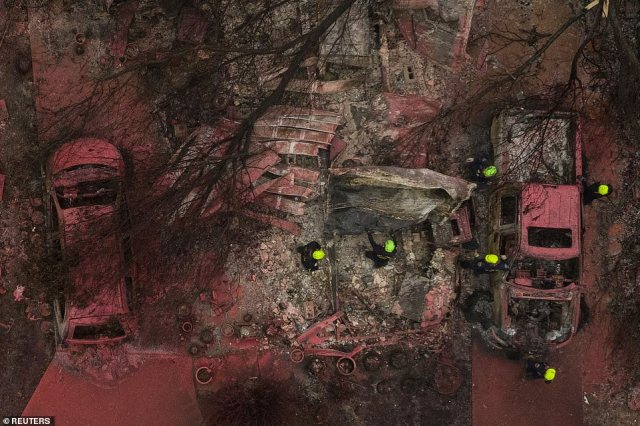 A search and rescue team, surrounded by red fire retardant, look for victims under burned residences and vehicles in the aftermath of the Almeda fire in Talent, Oregon on Sunday