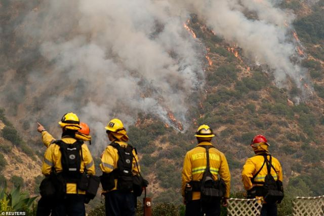 Firefighters watch the Bobcat Fire after an evacuation was ordered for the residents of Arcadia, California on Sunday