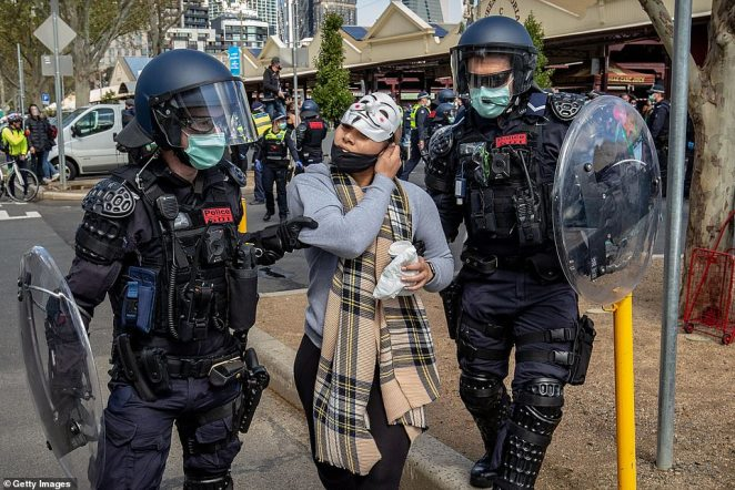 Police officers doing their best impersonation of the cover of the original Mad Max video tape arrest a woman on Sunday