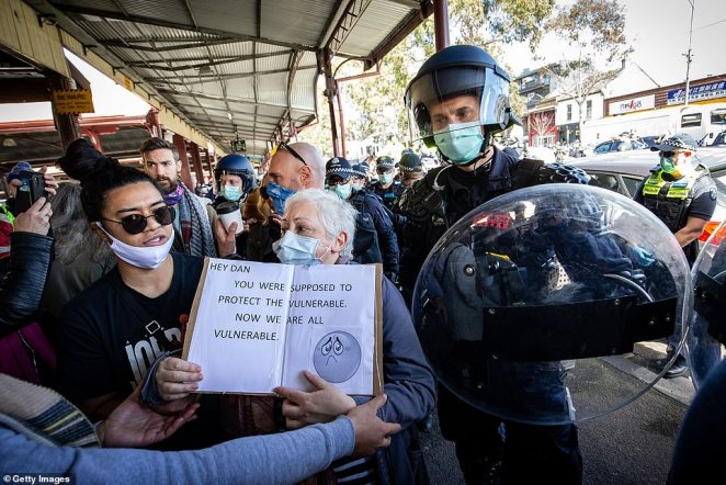 A woman attempts to protest at the Queen Victoria Market on Sunday where police made dozens of arrests and issued 176 fines