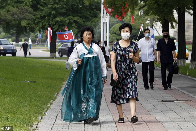 The even more repressive North Korean hermit kingdom sealed off its border city of Kaesong for just three weeks. Pictured are women holding national flags in the capital Pyongyang on September 9, 2020