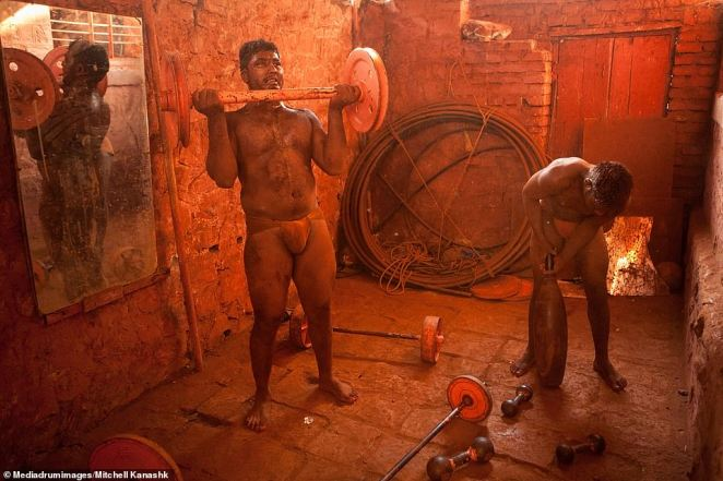 Kushti wrestlers perform barbell curls as part of their strict weight-training regime. The wrestlerspreach a life of total discipline, practicing celibacy as well as alcohol and tobacco abstinence