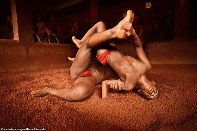 A man tackles a young boy to the ground and pins him upside down during an intense Kushti training sessionin Kolhapur, India