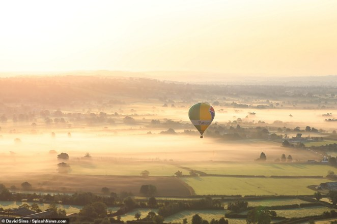 A balloon rises out of early morning mist on a day when an Indian summer hits the UK for the next week at least