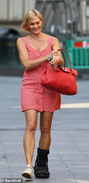 Dressed to impress: Despite her injury, the blonde beauty appeared to be in an upbeat mood, flashing a broad smile as she arrived in a plunging red summer dress