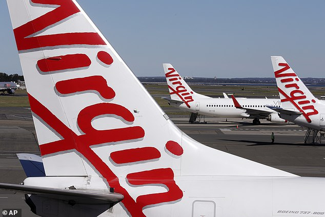 Virgin Australia is set to retrench 250 head office staff as continuing state border closures severely curtail its finances. Pictured are Virgin planes grounded in Sydney