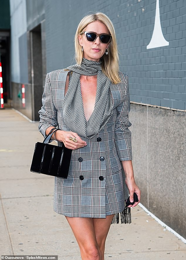 Tailored: The 36-year-old hotel heiress opted for a gray plaid coat dress with matching wraparound scarf