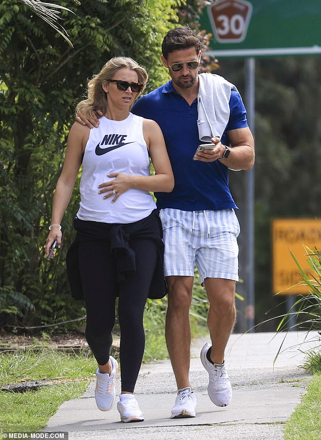Casual stroll:The criminal lawyer dressed casually for the outing in a white Nike singlet top teamed with black leggings and a jumper tied around her waist