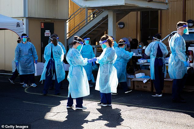 Seven new cases of COVID-19 were diagnosed in New South Wales on Tuesday. Pictured: Health care workers at a pop-up COVID-19 testing clinic in Sydney