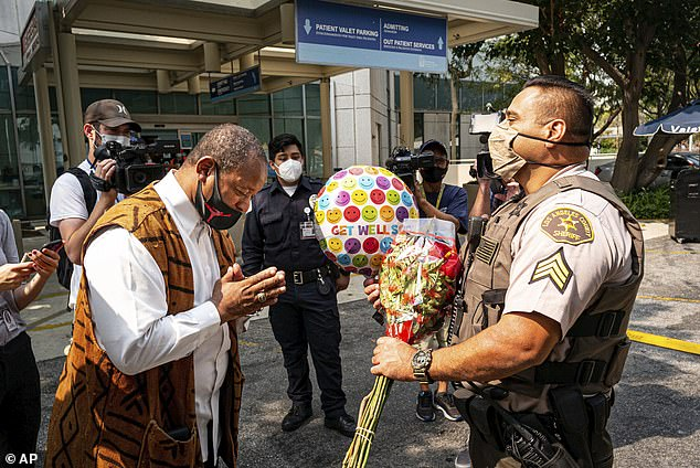 Najee Ali, of Project Islamic Hope, presents Sgt. Larry Villareal, of the Los Angeles County Sheriff Dept., flowers for deputies recovering at St. Francis Medical Center on Monday