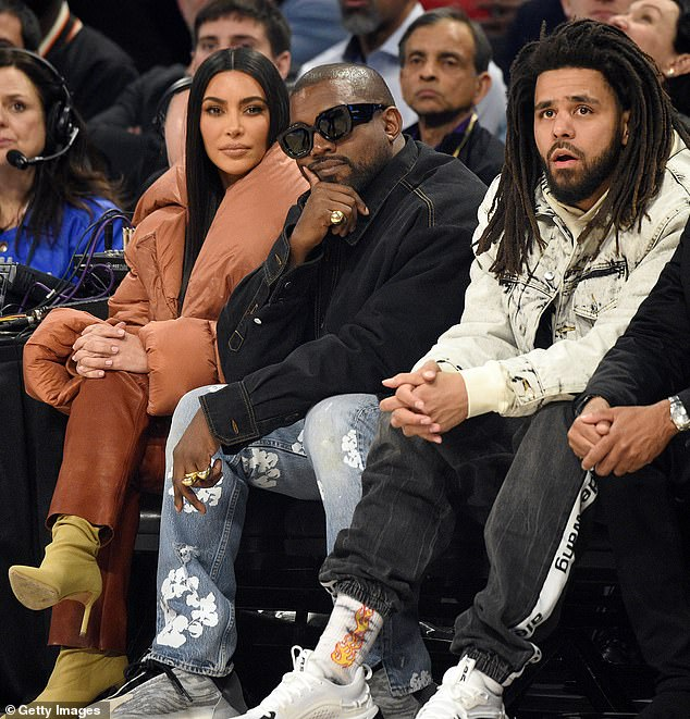 Kim Kardashian West, Kanye West, and J. Cole are pictured watching basketball in February