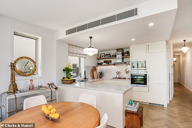 Open plan: The roomy open plan living area features a white kitchen along with a mix of art deco light fittings and downlights