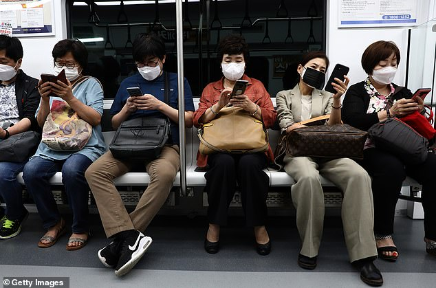 South Koreans wearing masks on a Seoul subway train on Tuesday as restrictions are loosened this week following a gradual decline in cases